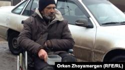 Мүгедектер арбасында қайыр сұрап отырған адам. Астана, 18 наурыз 2013 жыл. Көрнекі сурет.
