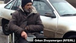 Человек в инвалидной коляске просит милостыню. Астана, 18 марта 2013 года. Иллюстративное фото.