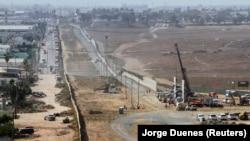 Люди (справа) работают над прототипом стены Трампа на границе с Мексикой в Сан-Диего, Калифорния. Фотография сделана в Тихуане, Мексика. 3 октября 2017 года.