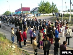 Жители поселка Шанырак под Алматы говорят с вооруженными полицейскими. 14 июля 2006 года.