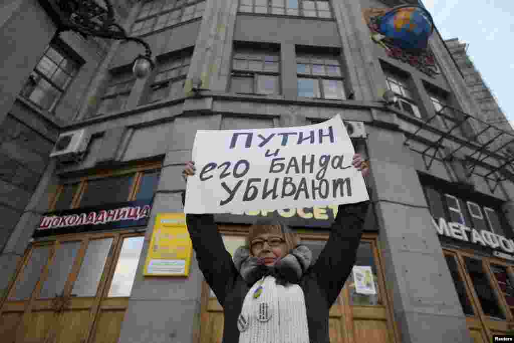 """Бір кісілік наразылық пикетінде """"Путин мен оның бандасы өлтіріп жатыр"""" деген жазу ұстап тұрған әйел адам. Мәскеу, 19 сәуір 2015 жыл."""