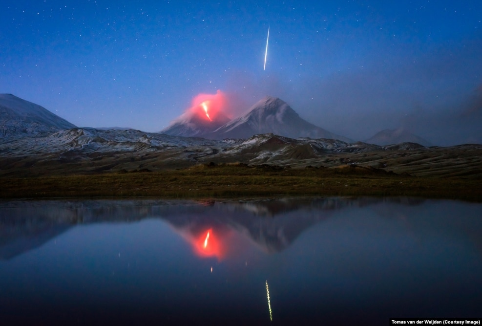 "Layers and layers of wonderful luck led to this photo of a meteor streaking above a volcano in Russia's Kamchatka Peninsula. Landscape photographer Tomas van der Weijden was on a photography tour that coincided with an eruption of Klyuchevskaya Sopka, a volcano that had lain dormant for two years. After the group heard news of the eruption they made their way to a vantage point but, wrapped in cloud, could see nothing. ""We decided to wait one more hour, then the cloud just suddenly lifted and we could see the lava flow in the darkness,"" says Van der Weijden. The Dutch photographer clicked the shutter for a 15-second exposure, and ""there was this huge green and white flash ... people screamed, actually. I thought: 'I hope I got that,' and I did. It was a wonderful moment."""