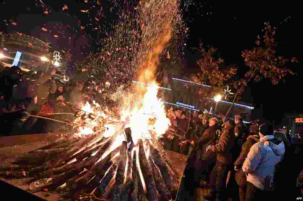 People attend a ceremonial burning of dried oak branches, a Yule log symbol, for Orthodox Christmas Eve in front of a church in Smederevo, 60 kilometers east of Belgrade, Serbia.