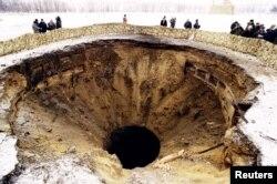 Журналисты стоят у шахтной пусковой установки, которую разрушили в рамках отказа Украины от ядерного оружия по Будапештскому меморандуму (1996)