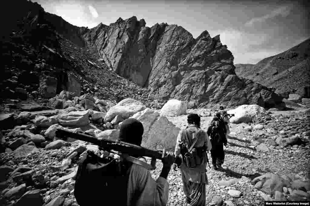 During the intense afternoon heat, Baloch Liberation Army guerillas travel along the floor of a valley in territory under their control.