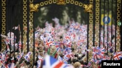 U.K. -- People wave British flags outside Buckingham Palace during the wedding of Prince William and Kate Middleton at Westminister Abbey, in central London, 29Apr2011