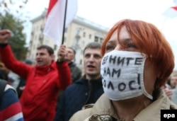 Opposition supporters shout slogans during a rally in Minsk on October 10, 2015.