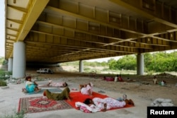 Hindu refugees from Pakistan rest under Signature bridge, a highway overpass, to avoid the summer heat near a Hindu refugee settlement situated in a woodland area in New Delhi.