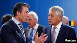 NATO Secretary-General Anders Fogh Rasmussen (left) talks to U.S. Defense Secretary Chuck Hagel during a NATO-Georgia defense ministers' meeting in Brussels in 2013.