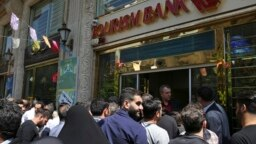 Iranians stand in front of a bank, hoping to buy U.S. dollars at a new official exchange rate announced by the government, in downtown Tehran, April 10, 2018