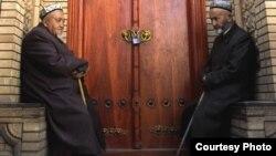Два мусульманина сидят перед дверьми мечети. Кашгар, Китай. Иллюстративное фото.
