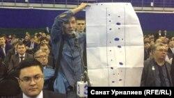 Гражданский активист Азамат Муханов демонстрирует плакат на отчетной встрече акима ЗКО. Уральск, 24 февраля 2016 года.