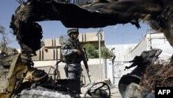 کماندوی پليس بغداد در کنار خودروی منفجر شده، بغداد پنجشنبه ۶ فروردين ۱۳۸۸
