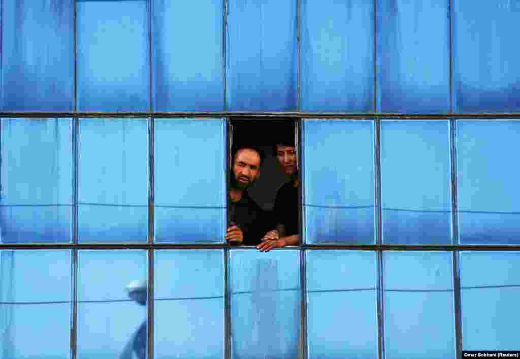 Afghan men look out of a window near the site of a suicide bomb blast in Kabul on August 15. (Reuters/Omar Sobhani)