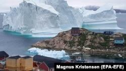 Айсберг и небольшое село в Гренландии.