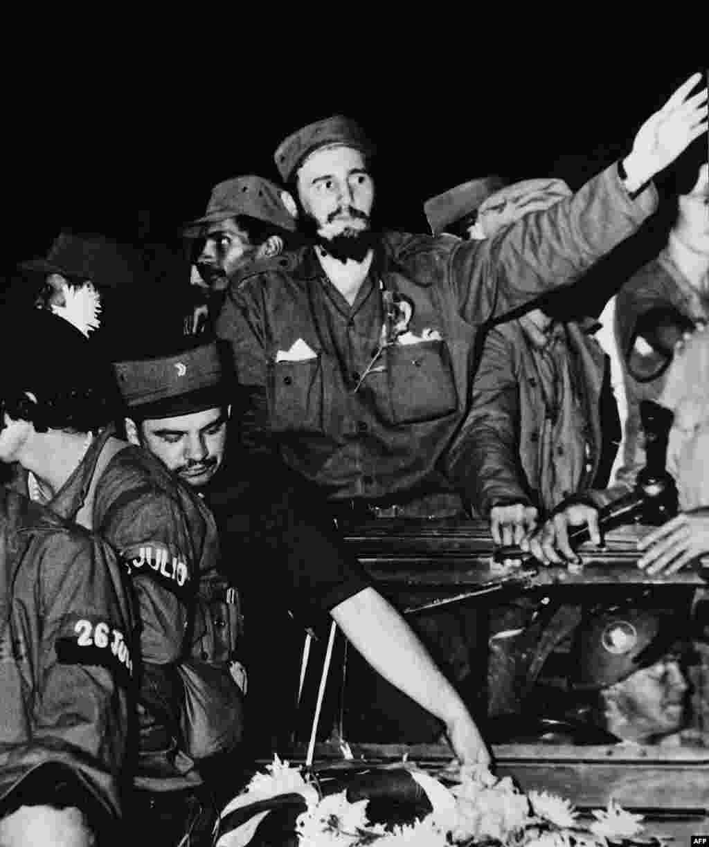 Surrounded by members of his leftist guerrilla movement, Castro (center) waves to crowds in Cienfuegos shortly after ousting Cuban dictator Fulgencio Batista in 1959.