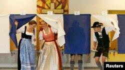 Disa zgjedhës të veshur me rroba tradicionale të Bavarisë duke votuar