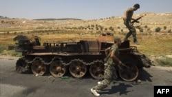 مخالفان مسلح حکومت بشار اسد در حال عبور از کنار یک تانک منهدم شده نیروهای دولتی سوریه