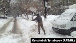 Қар күреп жатқан адам. Алматы, 20 қараша 2016 жыл.