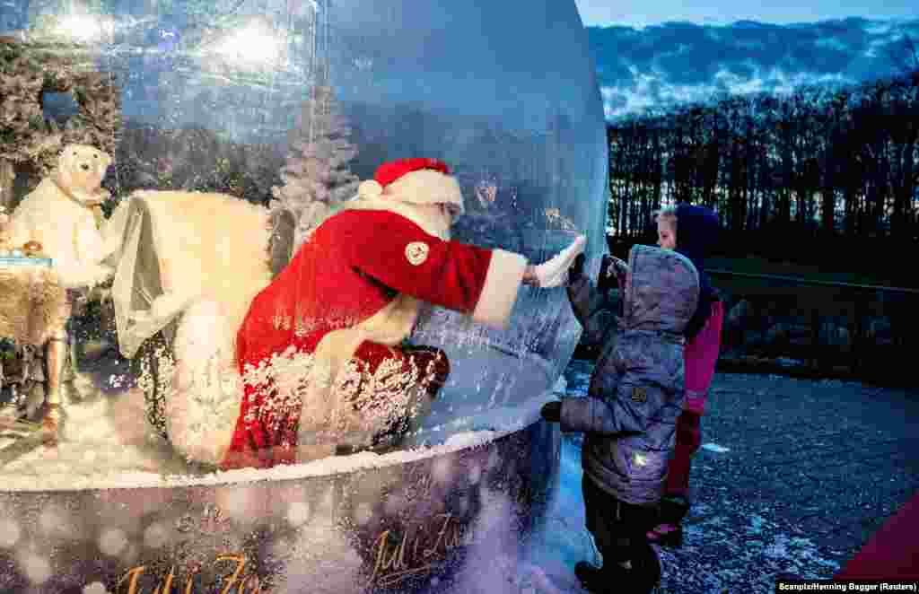 Мужчина в костюме Санта-Клауса встречается с детьми, сидя в «пузыре Санта-Клауса» на открытии рождественского сезона в зоопарке Ольборг, Дания, 13 ноября 2020 года