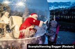 Санта-Клаус, приветствующий детей через оргстекло в датском городе Аальборг. Декабрь 2020 года