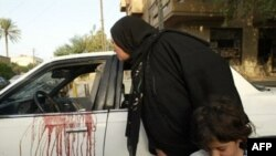 An Iraqi woman looks inside the blood-stained car of two women allegedly killed by Blackwater agents in central Baghdad in October 2007.