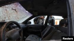 Афганские полицейские исследуют автомобиль у здания избирательной комиссии в Кабуле, на которое было совершено нападение. 25 марта 2014 года.