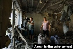 Two women examine their destroyed flat after fighting between Russia-backed separatists and Ukrainian government troops in the town of Yasinovataya in the eastern Donetsk region on August 1.