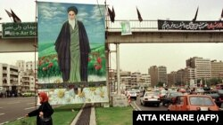 An Iranian woman passes a huge portrait of late Ayatollah Khomeini, 07 June, 1999 in Tehran, as Iran commemorates the tenth anniversary of the Ayatollah's death.