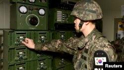 Оңтүстіккореялық солдат дауыс зорайтқышты қосып жатыр. Оңтүстік Корея шекарасы маңы, 8 қаңтар 2016 жыл.