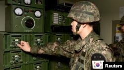 Южнокорейский военнослужащий включает громкоговорители в районе Йончона, 8 января 2016 года