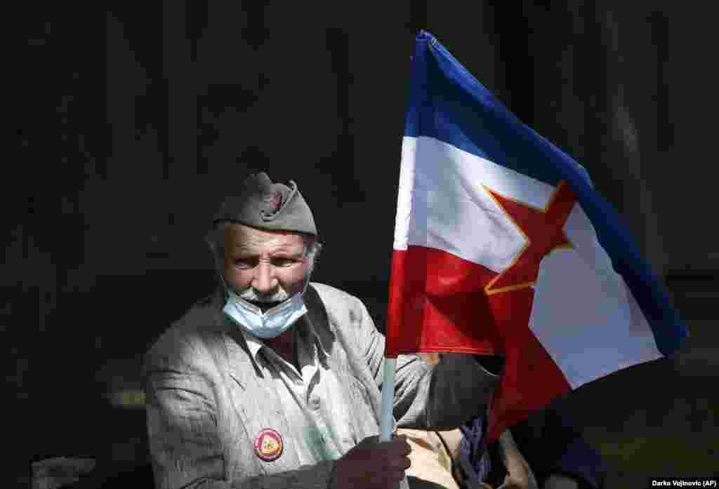 Сторонник Иосипа Броз Тито держит старый югославский флаг перед церемонией возложения венка в Белграде 25 мая по случаю 129-й годовщины со дня рождения покойного коммунистического диктатора