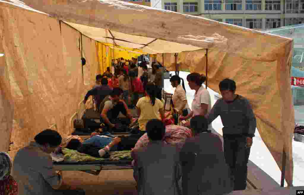 Injured residents of Minxian district in Gansu receive treatment in an emergency tent outside a hospital.