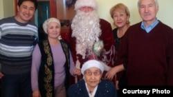 110 жасқа келген қарт ана Қызылгүл Боранбаева (бірінші қатарда) отбасымен бірге. Қызылорда, Тасбөгет кенті, 10 қаңтар 2012 жыл. Сурет жеке мұрағаттан алынған.