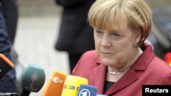 German Chancellor Angela Merkel talks to the media as she arrives at a European Union leaders summit in Brussels on October 24.