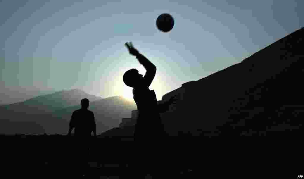 Afghan boys play volleyball as the sun sets in Kabul. (AFP/Wakil Kohsar)