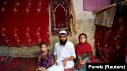 مهرالله صافی سرباز معلول اردوی ملی افغانستان همراه با دو طفلش در شهر جلال آباد مرکز ولایت ننگرهار.