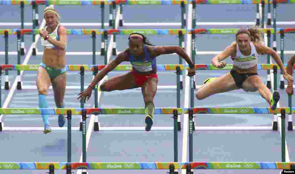 Ekaterina Voronina of Uzbekistan (left to right), Evelyn Aguilar of Colombia, and Ivona Dadic of Austria compete in the women's heptathlon 100-meter hurdles.