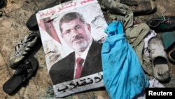 "A poster of deposed Egyptian President Muhammad Morsi that reads ""No to the coup"" lies amid the debris of a protest camp in Cairo."