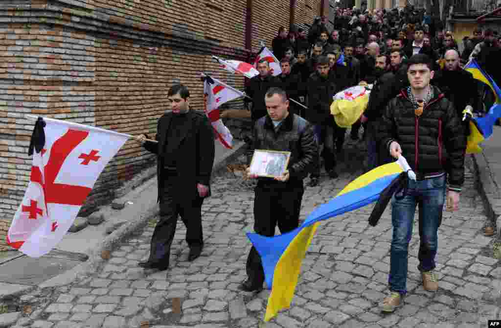 Carrying Georgian and Ukrainian national flags, people take part in the funeral of Dato Kipiani in Tbilisi, Georgia. Kipiani, a Georgian citizen and supporter of the Ukrainian opposition, was shot dead during protest rallies in the Ukrainian capital on February 20. (AFP/Vano Shlamov)