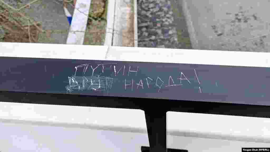 На парапеті з протилежного боку, розташованому над стелою з іменами почесних громадян міста, хтось нашкрябав вислів про Путіна