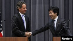 U.S. Treasury Secretary Timothy Geithner (left) shakes hands with Japan's Finance Minister Jun Azumi during a joint news conference at the Finance Ministry in Tokyo on January 12.
