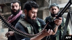 Syria -- A rebel fighter loads his machine gun during fightings with regime forces in the Sheikh Maqsoud neighborhood of Aleppo, 01Apr2013
