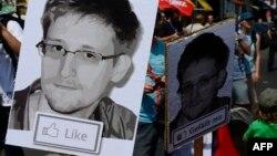 АҚШ ұлттық қауіпсіздік агенттігіне наразылық акциясына шыққандар осы агенттіктің бұрынғы қызметкері Эдвард Сноуденнің суретін ұстап тұр. Берлин, Германия, 27 шілде 2013 жыл.