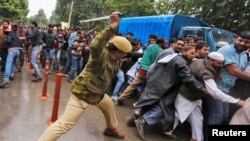 An Indian policeman uses a baton to disperse demonstrators during a protest by government employees demanding their long pending arrears and a regularisation of their temporary jobs, according to protesters, in Srinagar, on May 24.