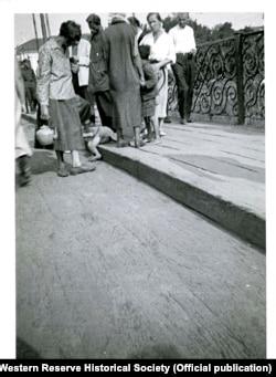 """Această fotografie făcută de Whiting Williams în august 1933 a apărut într-un articol pe care l-a scris pentru o revistă britanică un an mai târziu. Imaginea a fost uitată în mare măsură până acum. A fost publicat inițial cu legenda """"Femeile din fabrică trec pe lângă o mică victimă a foametei: un copil mort întins pe un trotuar din [Harkov]""""."""
