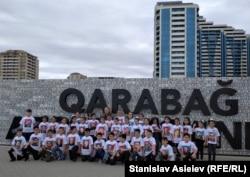 Азербайджанські діти позують на тлі стіни, викладеної з номерів спаленої вірменської техніки
