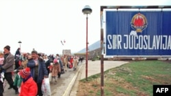 Kosovar refugees cross the border between Yugoslavia and Albania in April 1999.