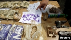 Полицейский показывает на наркотики, конфискованные во время межэтнических столкновений в Оше. 24 июня 2010 года.