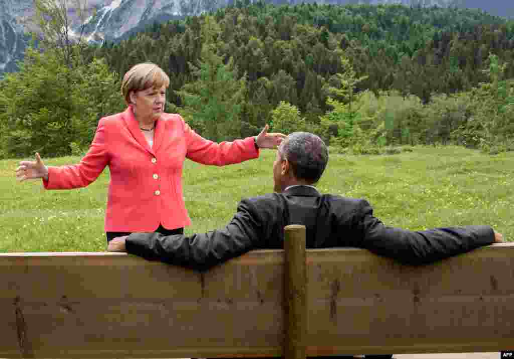 German Chancellor Angela Merkel (left) gestures while chatting with U.S. President Barack Obama sitting on a bench outside the Elmau Castle after a working session of a G7 summit near Garmisch-Partenkirchen on June 8. (AFP/Pool/Michael Kappeler)